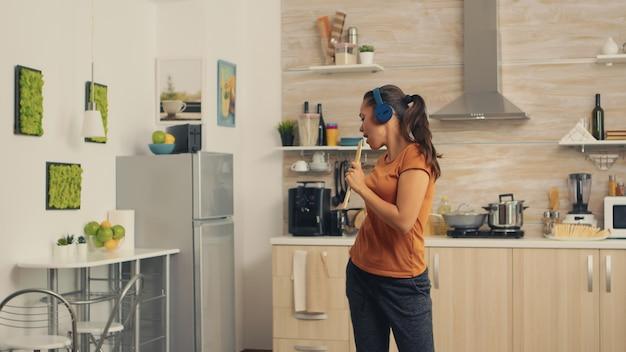 Młoda kobieta słuchania muzyki na słuchawkach śpiewa na drewnianą łyżką w kuchni. energiczna, pozytywna, szczęśliwa, zabawna i urocza gospodyni tańcząca samotnie w domu. rozrywka i wypoczynek samemu w domu