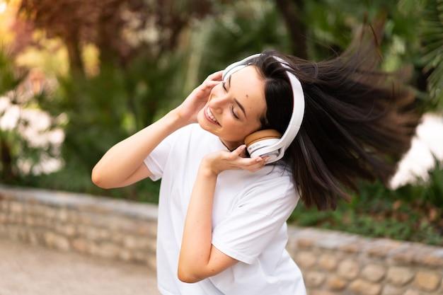 Młoda kobieta słuchania muzyki na zewnątrz