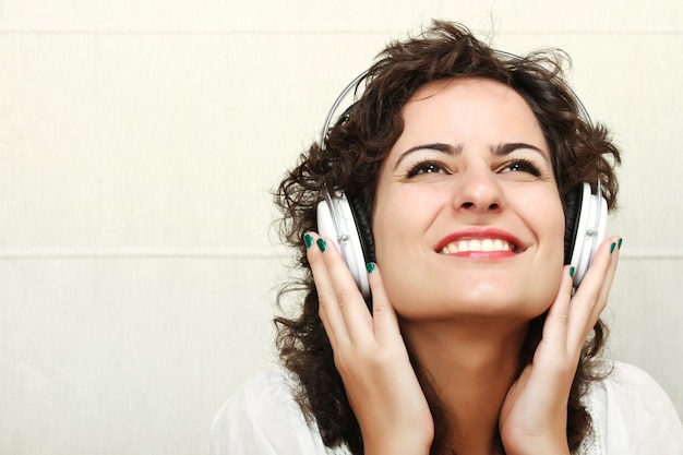 Młoda kobieta słuchania muzyki przez słuchawki.