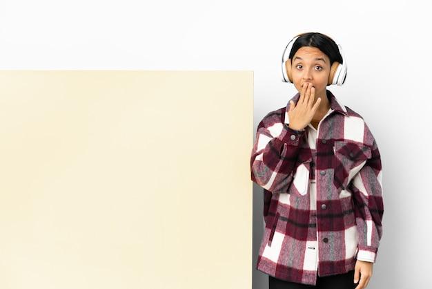 Młoda kobieta słuchania muzyki z dużym pustym plakietką na białym tle obejmujące usta ręką