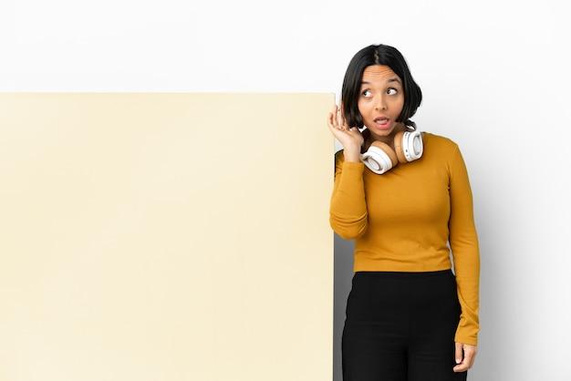 Młoda kobieta słuchania muzyki z dużym pustym plakietką na białym tle słuchając czegoś, kładąc rękę na uchu