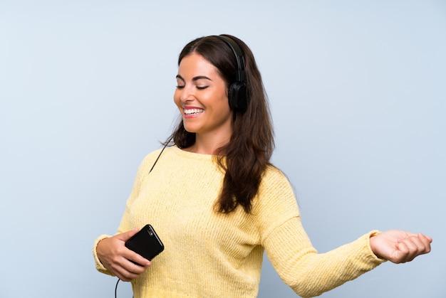 Młoda kobieta słuchania muzyki z ruchomą niebieską ścianą i taniec