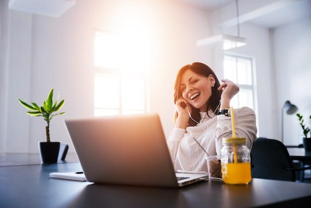 Młoda kobieta słuchanie muzyki podczas pracy na laptopie w biurze.