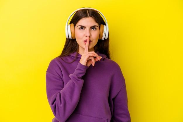 Młoda kobieta, słuchanie muzyki w słuchawkach na białym tle na różowej ścianie, zachowując tajemnicę lub prosząc o ciszę