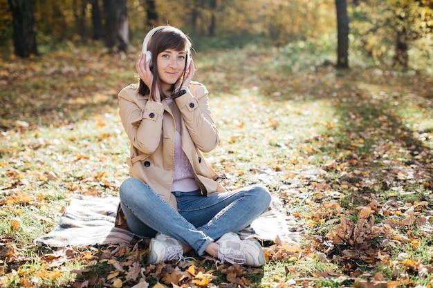 Młoda kobieta, słuchanie muzyki w słuchawkach w lesie jesienią