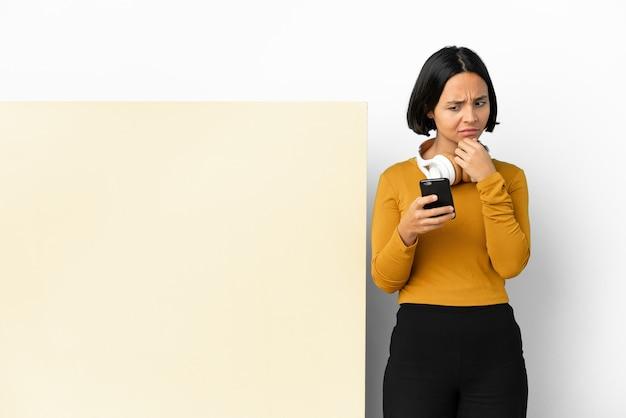 Młoda kobieta słuchanie muzyki z dużym pustym plakatem na białym tle myślenia i wysyłanie wiadomości