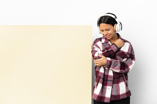 Młoda kobieta słuchanie muzyki z dużym pustym plakatem na białym tle z bólem łokcia