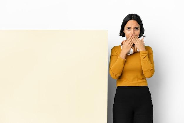 Młoda kobieta słuchanie muzyki z dużym pustym plakietką na białym tle obejmujące usta rękami