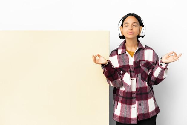 Młoda kobieta słuchanie muzyki z dużym pustym plakietką na białym tle w pozie zen