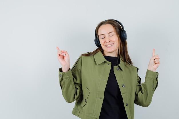 Młoda kobieta słuchanie muzyki ze słuchawkami w zielonej kurtce i patrząc rozbawiony, przedni widok.