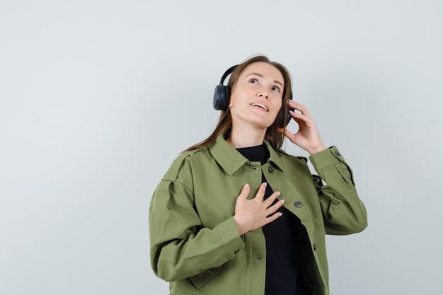 Młoda kobieta słuchanie muzyki ze słuchawkami w zielonej kurtce i patrząc zadowolony, widok z przodu.