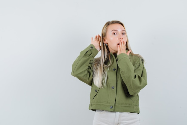 Młoda kobieta słyszy coś w zielonej kurtce i wygląda na zaskoczoną. przedni widok.