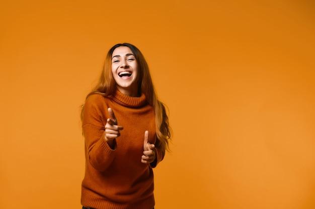 Młoda kobieta śmia się wskazuje palce z przodu