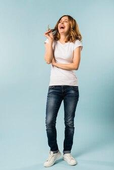 Młoda kobieta śmia się z radością przeciw błękitnemu tłu