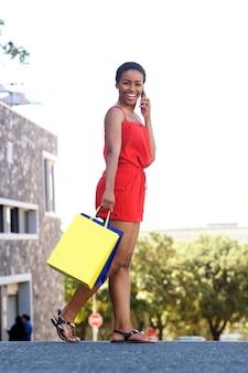 Młoda kobieta śmia się z torba na zakupy i telefonem komórkowym