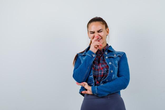 Młoda kobieta śmiejąc się podczas pozowanie w kraciastą koszulę, kurtkę, spodnie i wyglądając na szczęśliwą. przedni widok.