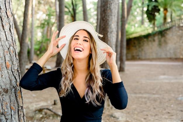 Młoda kobieta śmieje się ze szczęścia, stwarzając zabawę w kapeluszu.