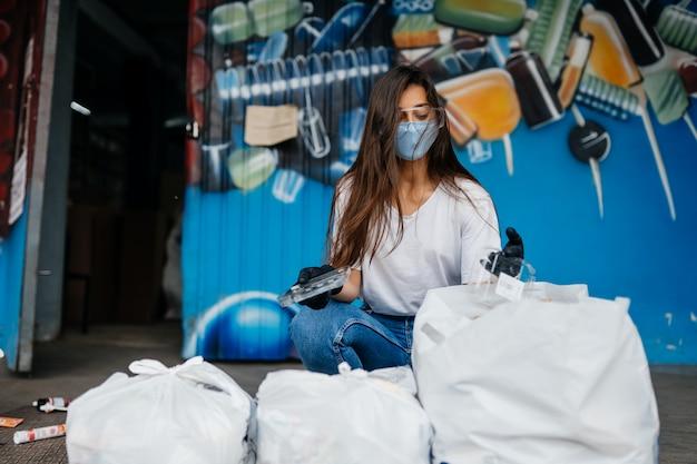 Młoda kobieta sortowania śmieci. pojęcie recyklingu. zero marnowania