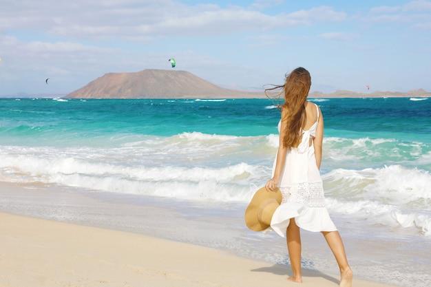 Młoda kobieta spaceru na dzikiej plaży corralejo, fuerteventura, wyspy kanaryjskie