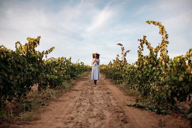 Młoda kobieta spaceru na ścieżce po środku winnicy