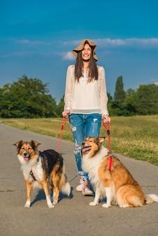 Młoda kobieta spaceru psy w parku