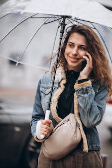 Młoda kobieta spaceru w deszczu z parasolem