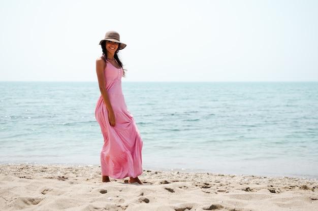 Młoda kobieta spaceru wzdłuż plaży z różowej sukience