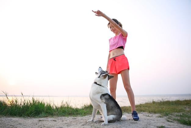Młoda kobieta spaceru z husky nad rzeką
