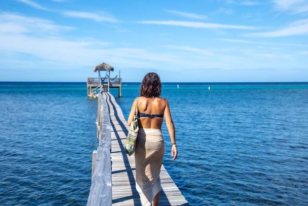 Młoda kobieta spacerująca drewnianym chodnikiem wzdłuż plaży sandy bay na wyspie roatan. honduras