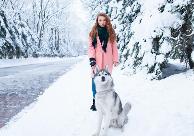 Młoda kobieta spaceruje po parku z siberian husky