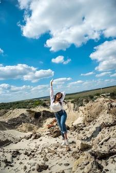 Młoda kobieta spaceruje wśród piasków pustyni lub kamieniołomu z błękitnym niebem, idealny styl życia na łonie natury