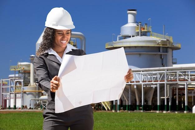 Młoda kobieta specjalista budowy przeglądu planów na budowie