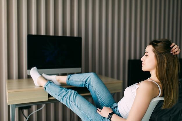 Młoda kobieta spędza czas na relaks w domu, siedząc z bosymi stopami na stole i zamkniętymi oczami