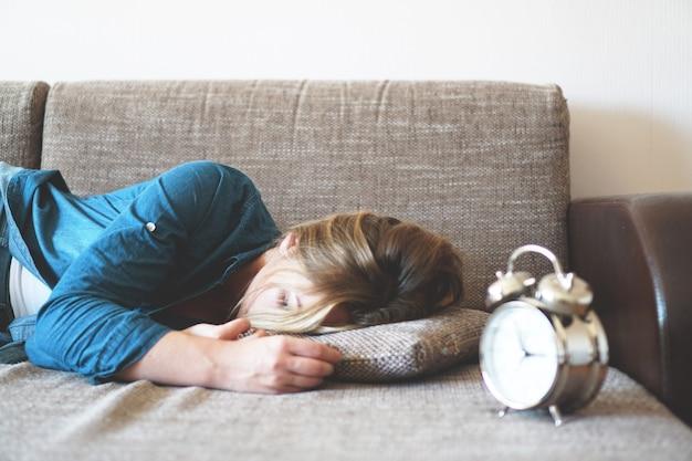 Młoda kobieta śpi i budzik w sypialni w domu. styl życia