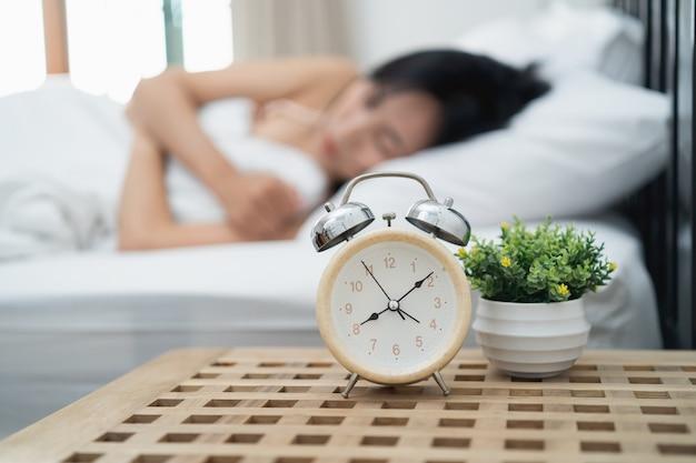 Młoda kobieta śpi i budzik w sypialni w domu