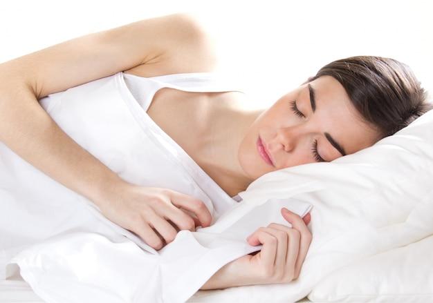 Młoda kobieta śpi samodzielnie na białym tle