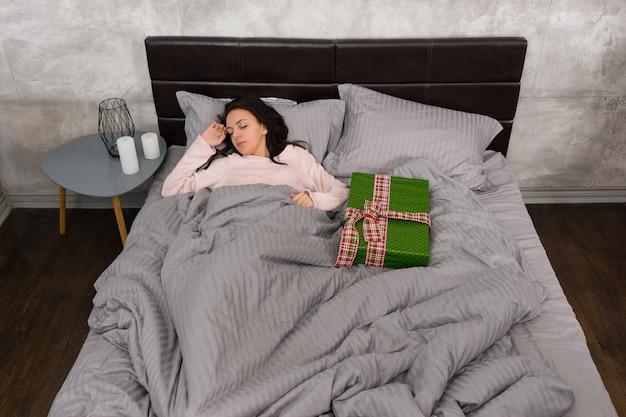 Młoda kobieta śpi w piżamie w łóżku z prezentem świątecznym w sypialni w stylu loftu w szarych kolorach