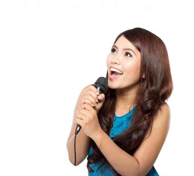 Młoda kobieta śpiewa, trzymając mikrofon, na białym tle