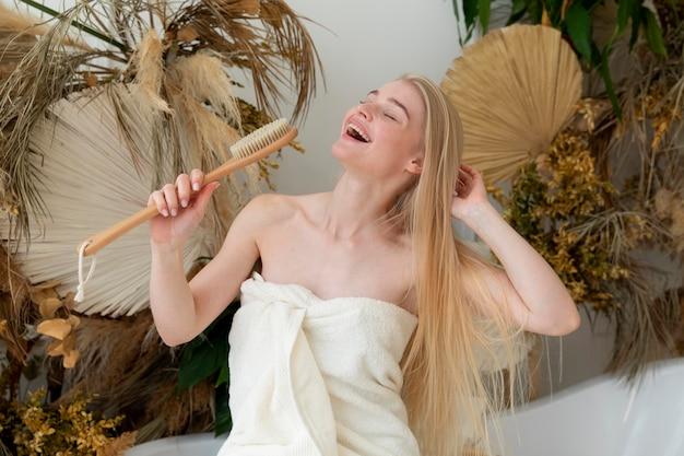 Młoda kobieta śpiewa trzymając szczoteczkę do ciała