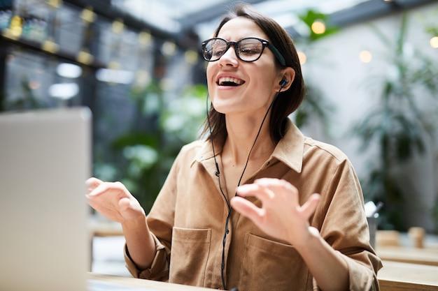 Młoda kobieta śpiewa ulubioną piosenkę w miejscu pracy