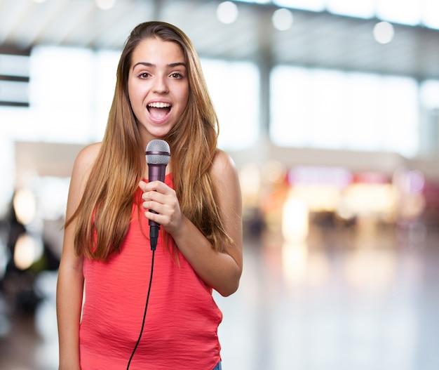 Młoda kobieta śpiewa z mikrofonem na białym tle