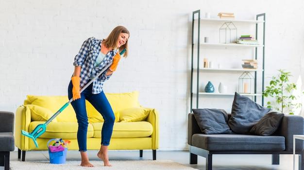 Młoda kobieta śpiewa z mopem podczas czyszczenia pokoju