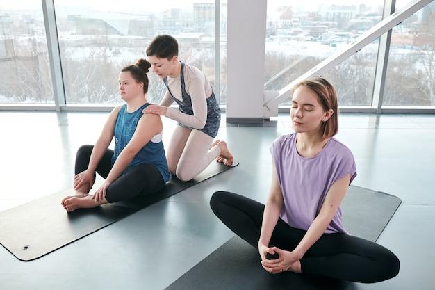 Młoda kobieta spokojny z zamkniętymi oczami siedzi na macie podczas relaksujących ćwiczeń jogi