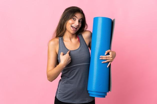 Młoda kobieta sport idzie na zajęcia jogi, trzymając matę na białym tle na różowej ścianie z wyrazem twarzy zaskoczenia