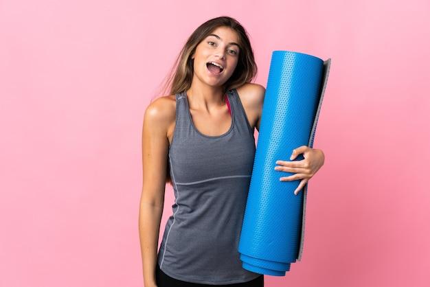 Młoda kobieta sport idzie na zajęcia jogi, trzymając matę na różowo z zaskoczeniem i zszokowanym wyrazem twarzy