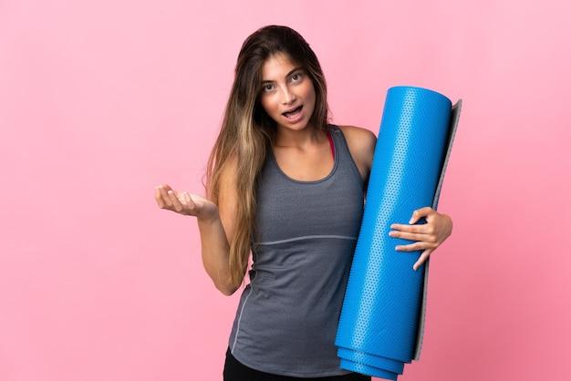 Młoda kobieta sport idzie na zajęcia jogi, trzymając matę na różowym tle z zszokowanym wyrazem twarzy