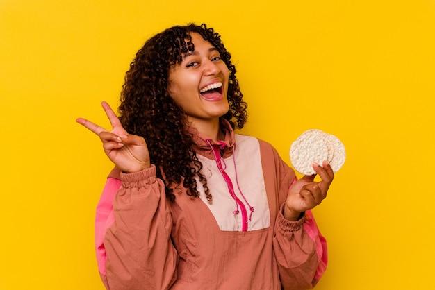 Młoda kobieta sport mieszanej rasy trzyma ciastka ryżowe na białym tle na żółtym tle radosny i beztroski pokazując palcami symbol pokoju.
