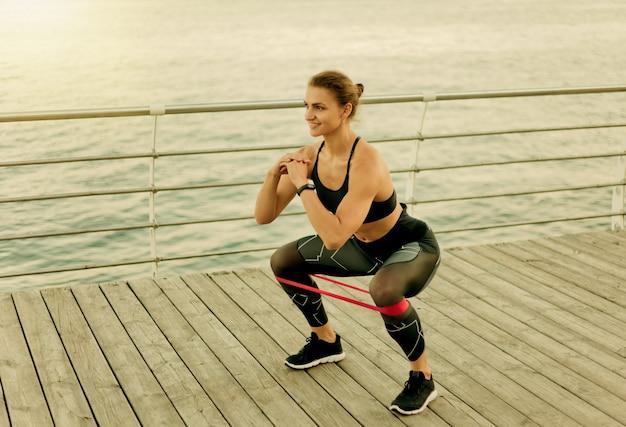 Młoda kobieta sport robi przysiady z gumką na tarasie plaży