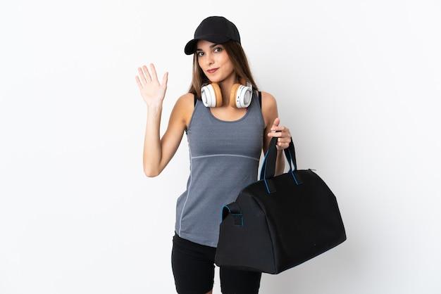 Młoda kobieta sport z torbą sportową na białym pozdrawiając ręką z happy wypowiedzi
