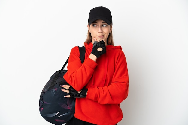 Młoda kobieta sport z torbą sportową na białym tle na białej ścianie, mając wątpliwości i myślenie